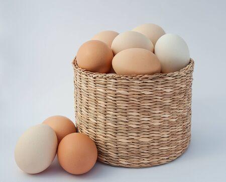 Chicken eggs in a wicker basket on a white background, three eggs lie beside Standard-Bild