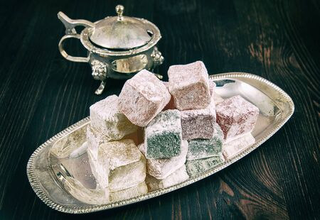 appetising: Rose flavoured Turkish delight in traditional silver bowl on wooden  background, vintage toning
