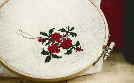 Hand embroidery cross-stitch flower ornament on a white fabric in the wooden embroidery frame red and black thread, vintage toning