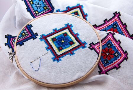Traditional Slavic geometric pattern embroidered cross stitch multicolored thread, white fabric in the wooden embroidery hoop