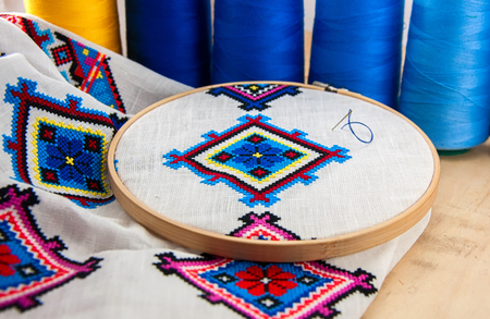 Traditional Slavic geometric pattern embroidered stitch cross on a white canvas with colored thread Stock Photo
