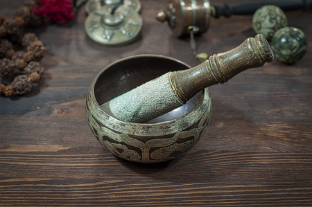 Singing Bowl against other religious ritual objects, brown wooden table Stock Photo