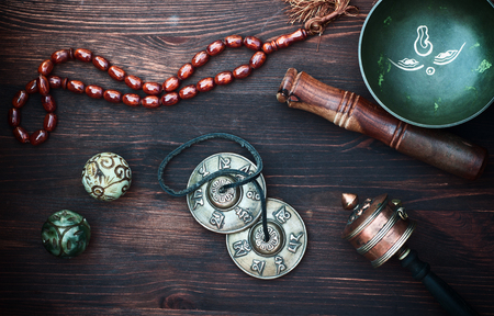 diverse ethnic objects for meditation and relaxation: singing bowl, strike plates, drums, beads and two balls, view from above