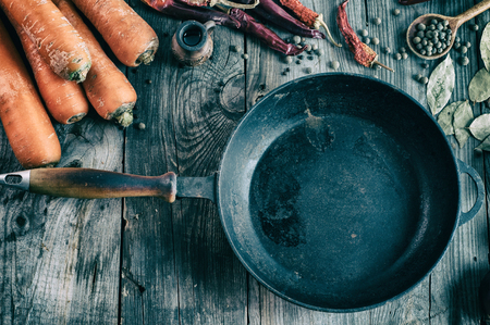 cast iron pan: Blank black cast iron pan among the fresh vegetables and spices on gray wooden surface, vintage toning