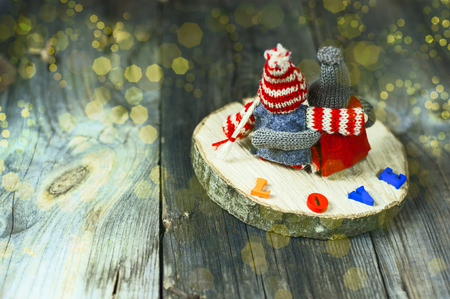 background of love and dreams with two wooden toys on gray surface and an inscription love, with a yellow background bokeh