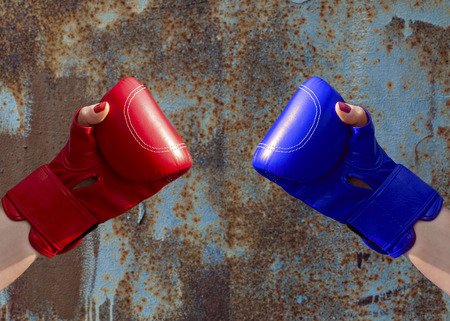 rusty nail: Two female hands in red and blue boxing gloves, hands are on opposite sides Stock Photo