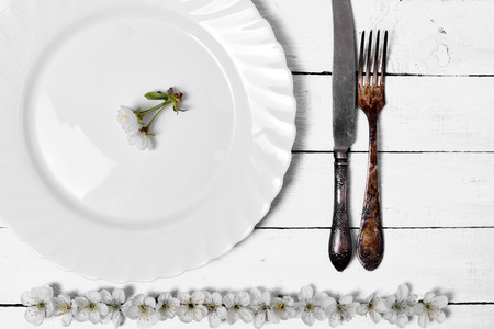 White empty plate with cutlery on a wooden surface, top view