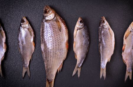 Dried fish is a ram of various sizes lies hardly on the black surface, the top view