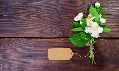 bouquet of blooming white jasmine with an empty paper tag on a brown wooden table, top view, empty space