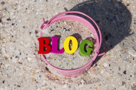 Word blog of wooden letters in a pink bucket with sand, summer day