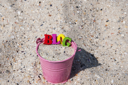 Word blog of wooden letters in a pink bucket with sand, top view