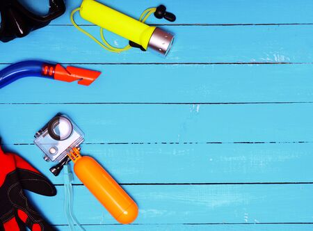 Set for underwater diving to depth on a blue wooden background, empty space on the right