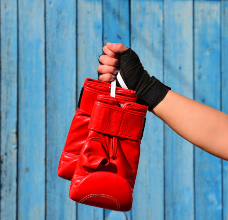 Red boxing gloves hanging on a rope in a womans hand, tied with a black bandage on a blue background
