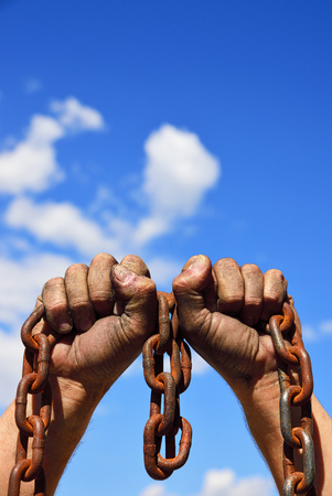Two mens hands in the mud hold a rusty metal chain against the sky