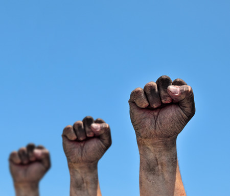 Three dirty male fists raised up on a blue background Stock Photo