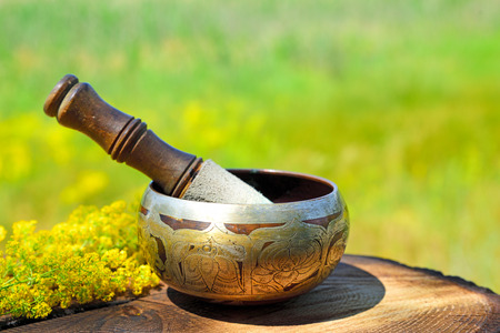 Copper singing bowl with a stick on a wooden table, blurred background of nature