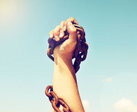 The female hand is lifted up and bound by an iron chain against the sky and the sun Imagens