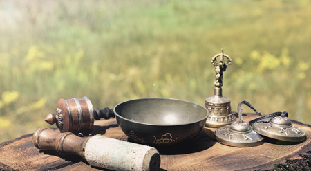 Singing bowl and other Tibetan religious objects on a wooden background Stock Photo