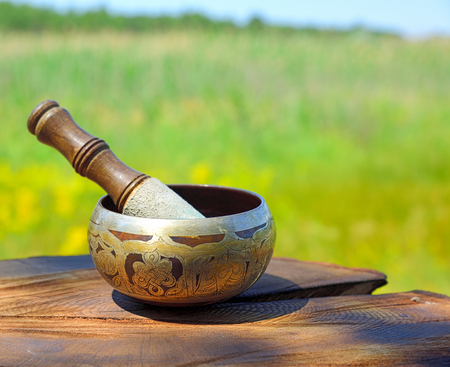 Copper Tibetan singing bowl on a brown wooden background, blurred background