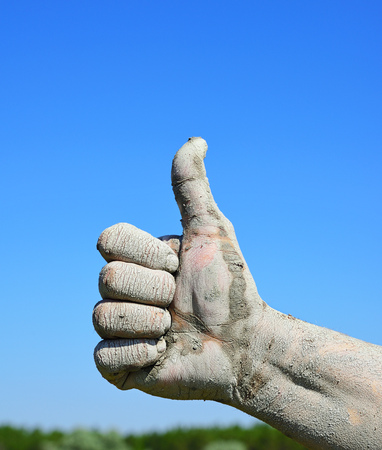 Male finger lifted up against the blue sky, an approving gesture