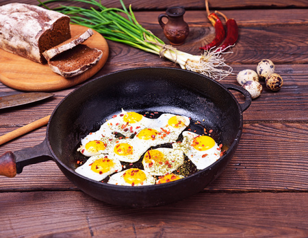 huevos de codorniz: Fried quail eggs in a black cast-iron frying pan on a brown wooden background