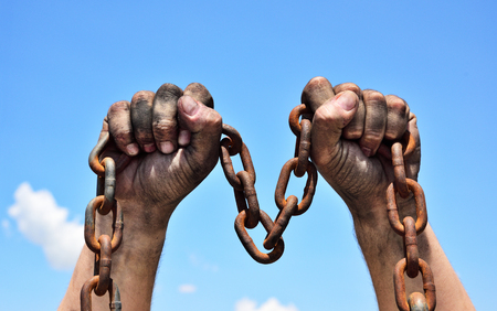 Two dirty male hands holding a rusty metal chain, arms raised Stock Photo