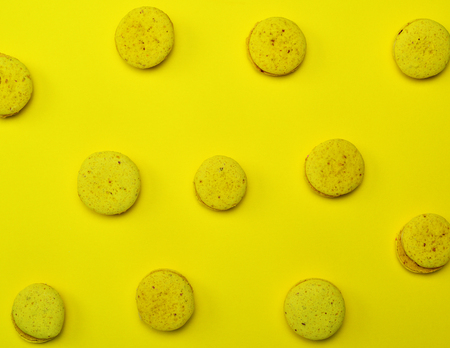 Yellow French cake made from egg whites and almond flour macarons  on a yellow background, top view
