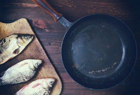cutting: Empty cast iron black frying pan with a wooden handle, next to the kitchen board three fresh river fish carp, top view