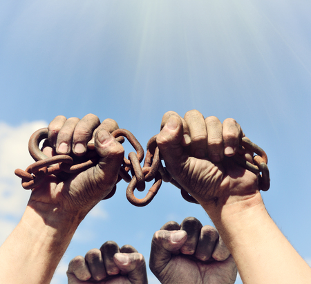 two dirty male hands wrapped in a rusty iron chain raised up against a blue sky and sun