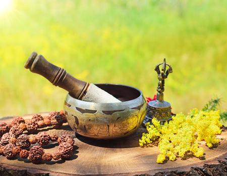 Tibetaanse koperen klankschaal en rozenkrans op houten stronk in de stralen van de zon Stockfoto