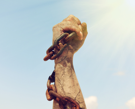 the female hand is wrapped in an iron rusty chain and raised up in the suns rays against the sky