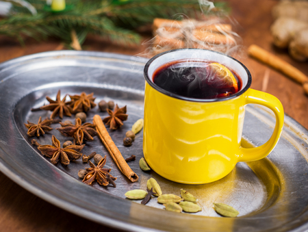 hot drink mulled wine in a yellow mug and dried star anise
