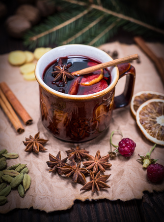 mulled wine in a brown ceramic cup on a brown sheet of paper with ingredients and spices
