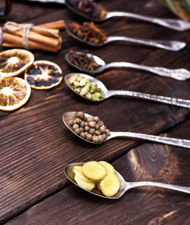 sliced ginger in an iron spoon and other spices