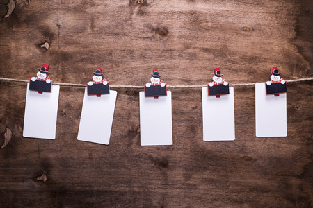 white paper tags hanging on a rope hooked on decorative christmas clothespins, brown wooden background