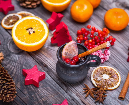 Mulled wine in a brown ceramic cup on a gray wooden background and Christmas decorations Stock Photo