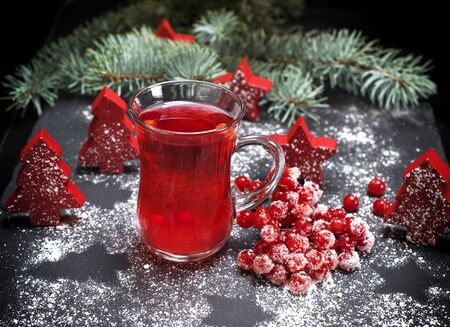 tea from fresh red viburnum in a transparent glass on a black background, near branch with red berries of viburnum in sugar
