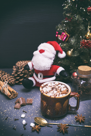 hot chocolate in a brown ceramic mug on a black background in the midst of a festive decor, vintage toning Stock Photo