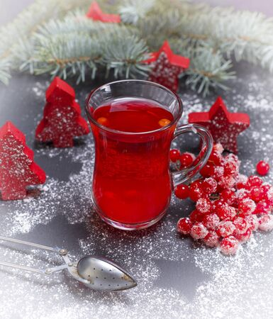 tea made from fresh berries of viburnum in a glass cup and fresh bunch of viburnum with red berries among the Christmas decor, vintage toning