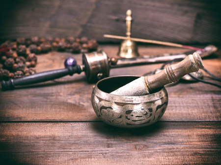 copper singing bowl and a wooden stick on a brown table, a vintage toning