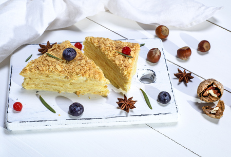 two baked cakes Napoleon with cream on a white wooden board, top view Stock Photo