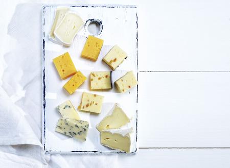 白い木製のボード上のクルミとブリーチーズ、ロックフォート、カマンベール、チェダーとチーズの小片、空きスペース