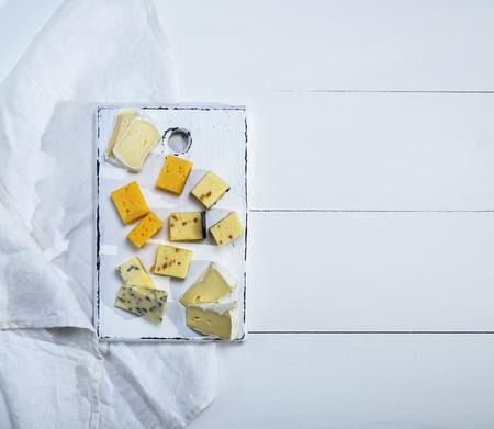 白い木製のボードにクルミとブリーチーズ、ロケフォート、カマンベール、チェダーとチーズの小片、空きスペース