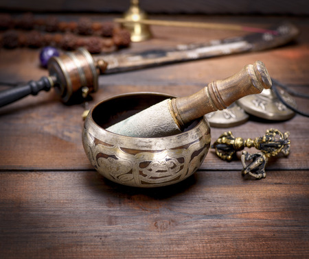 copper singing bowl and a wooden stick on a brown table, close up Stock Photo