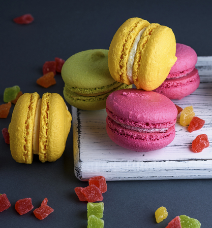 multicolored baked cakes of almond flour macarons on a white wooden board, black background, close up