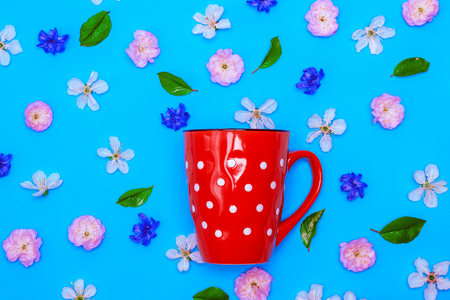 ceramic red mug  with white polka dots on a blue background amid the buds of white cherry and almond trilobate, over view