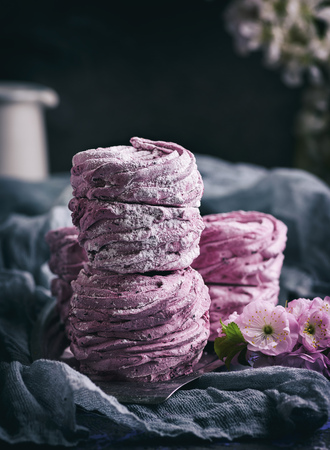 a stack of marshmallows with black currants on an iron plate, close up, vintage toning Stock Photo