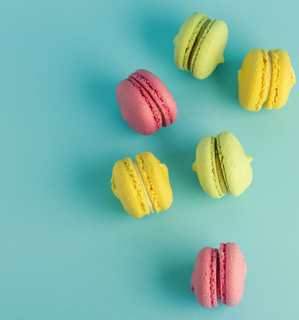 round multicolored pastry with almond flour macarons on a blue background, empty space on the left, top view