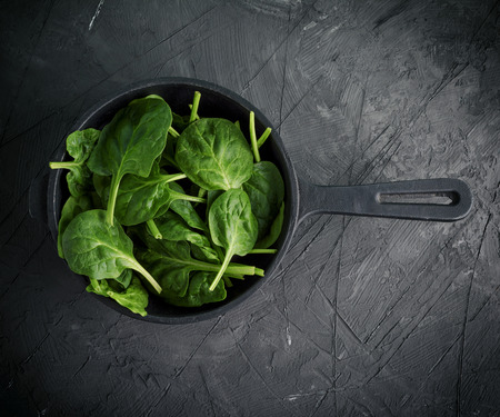fresh green leaves in a black round frying pan with a handle on a black textural background, top view