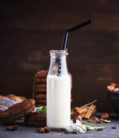 one full glass bottle with milk and a black straw, a number of chocolate shocks on a black surface Stock Photo